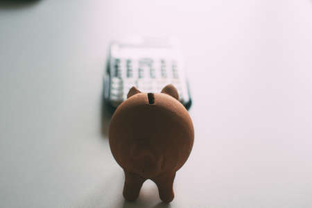 Piggy bank shaped piggy bank in front of calculator. Economy and finances of the home. Stock fotó