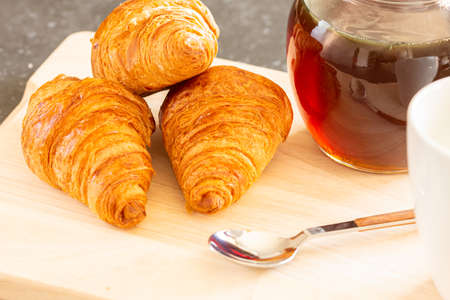 Fresh croissants, spoon and honey jar over wooden board