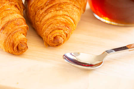 Close up of Fresh croissants, spoon and honey jar over wooden board, breakfast, selective focus Stock fotó