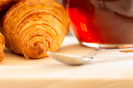 Close up and selective focus of Fresh croissants, spoon and honey jar over wooden board, breakfast, food background Stock fotó