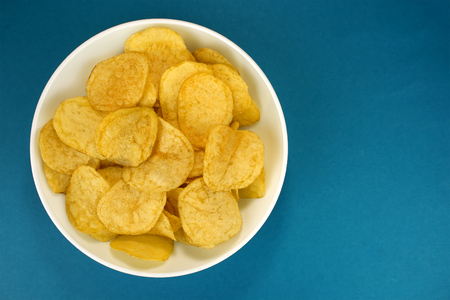 Potato chips on a blue background, top view
