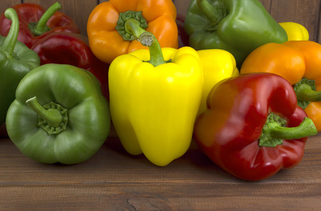 Assorted colorful varieties of sweet peppers sitting on old wooden table