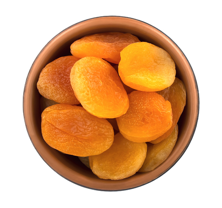 Bowl of dried apricots isolated on white background