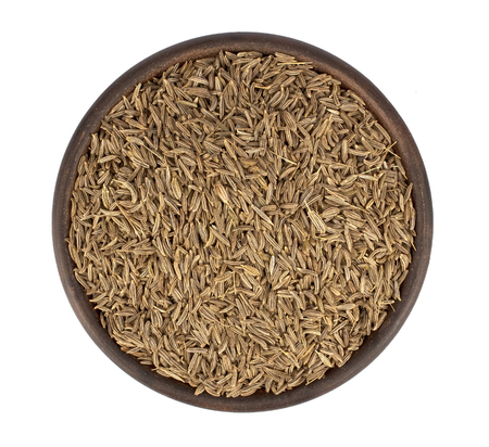 Cumin seeds into a bowl isolated in white background 版權商用圖片