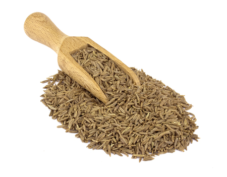 Food ingredients: heap of cumin in a wooden scoop, on white background