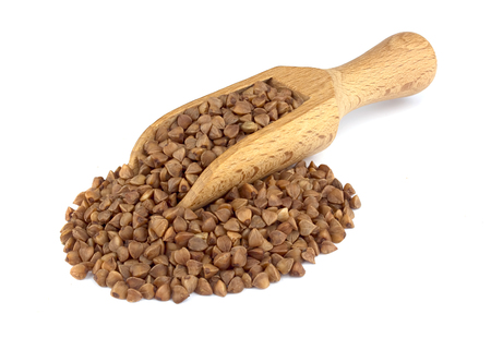 Food ingredients: heap of buckwheat in a wooden scoop, on white background