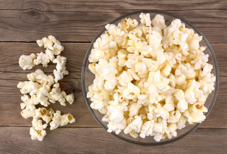 Popcorn in a bowl on a wooden table, top view Archivio Fotografico