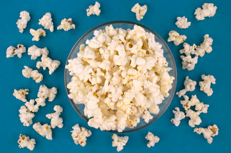 Popcorn in a bowl on blue background, top view