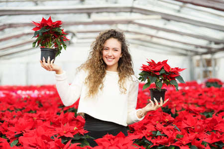 smiling woman in a greenhouse: florist