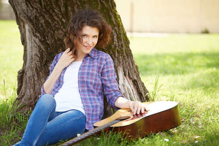 under a tree: girl playing guitar under a tree in the garden