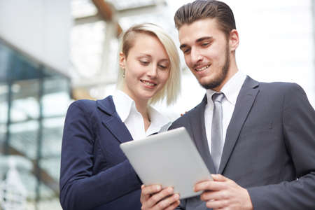 young entrepreneurs: smiling businessman and businesswoman with tablet pc computer over office building