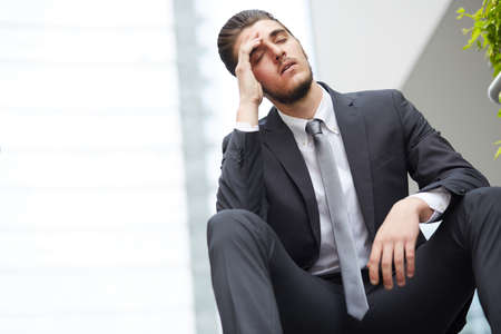 emotional pain: Young business man crying abandoned lost in depression sitting on ground street concrete stairs suffering emotional pain Stock Photo