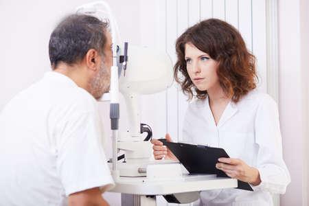 optometrist: Optometrist performing visual field test