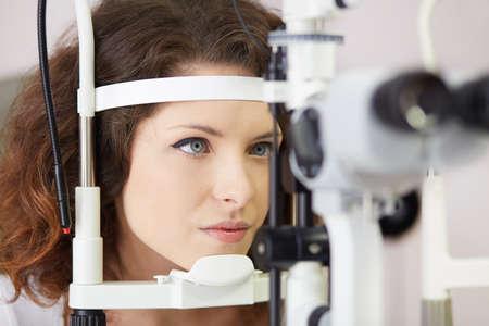 oculist: La mujer bonita está estudiando la máquina de prueba del ojo con la concentración en el laboratorio oculista
