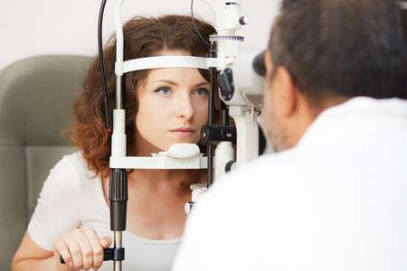 oculista: La mujer bonita está estudiando la máquina de prueba del ojo con la concentración en el laboratorio oculista