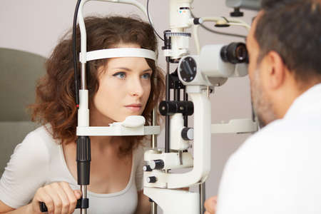 exam room: Optometrist in exam room with woman in chair