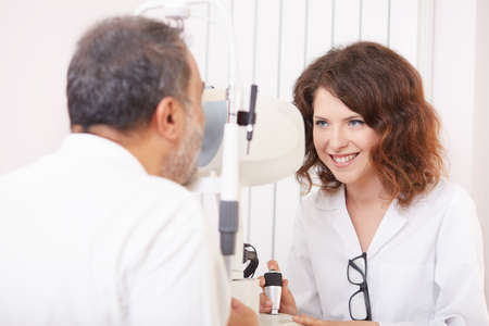optometrist: Optometrist in exam room with woman in chair