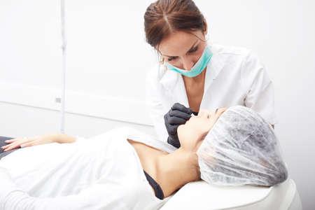 cosmetologist: Cosmetologist applying permanent make up on lips