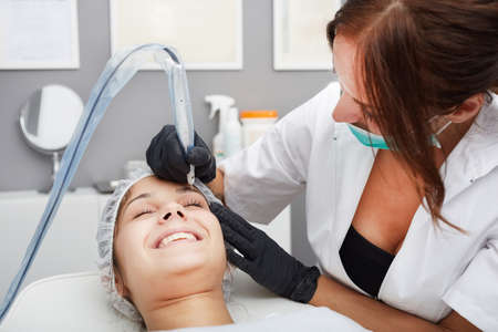 cosmetologist: Cosmetologist applying permanent make up on eyebrows Stock Photo
