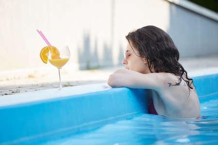 woman bath: Pretty brunette woman  enjoying cocktail in a swimming pool