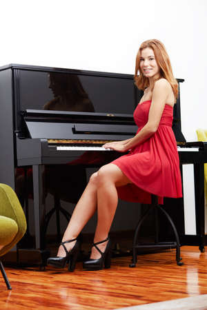 tilt views: Happy young woman playing piano indoors.