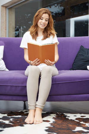 Smiling woman relaxing with a book  on a sofa