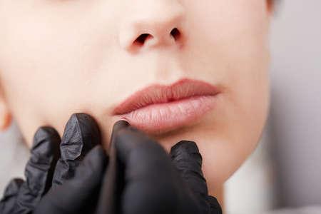 Cosmetologo applicando Trucco Permanente sulle labbra Archivio Fotografico - 66177794