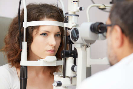 Woman doing eye test with optometrist in medical office