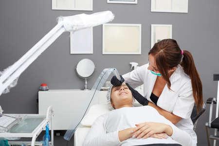 Cosmetologist applying permanent make up on eyebrows Standard-Bild