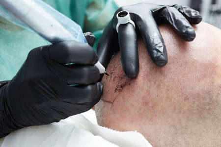 tatuador profesional haciendo maquillaje permanente tricopigmentation Foto de archivo