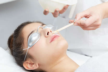 female beautician using laser machine on customer at salon
