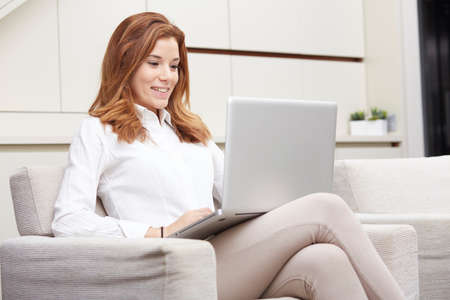 Happy young woman sitting in armchair with laptop computer