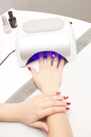 Hands with uv lamp for nails Stock Photo