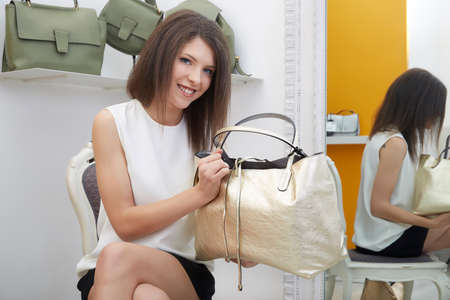 positiv: Woman trying bags and shoes sitting in a shop Stock Photo