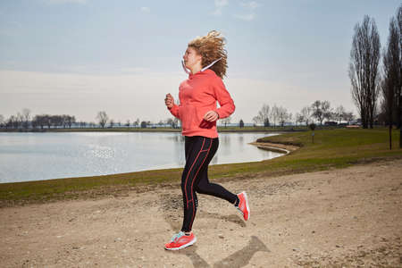 Fit woman running fast, training in bright sunshine Stock Photo