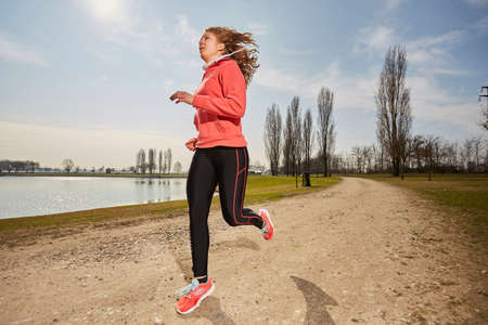 pace: Fit woman running fast, training in bright sunshine Stock Photo