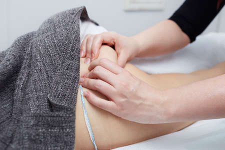 connective: Deep tissue massage on a womans hip gluteus muscles Stock Photo