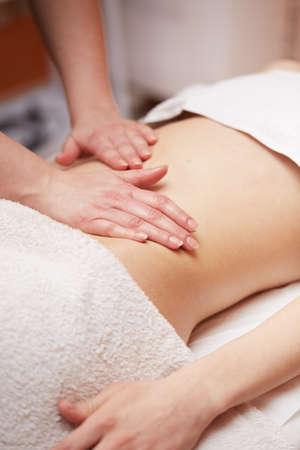 Una mujer recibe un masaje de vientre en el salón de spa
