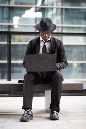 executive search: Serious business man working on laptop computer outdoors Stock Photo