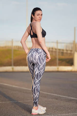 young female runner with perfect figure dressed in sport bra and shorts