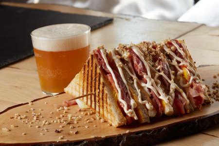club sandwich made with tomato, cheddar, mayonnaise, chopped walnuts, ham on wooden tray
