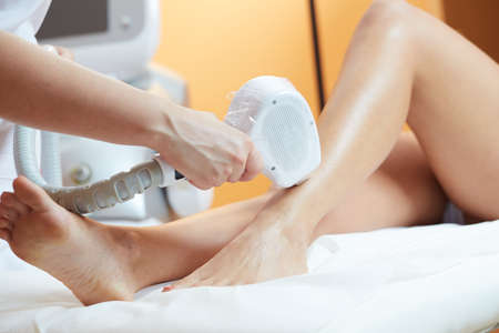 woman at cosmetics salon, legs laser epilation Stock Photo