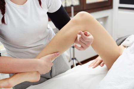 alternative practitioner: Therapist applying pressure on female leg