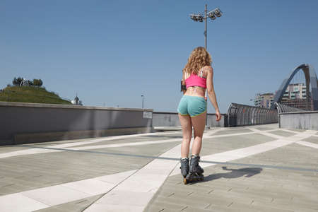 Skating woman on roller blades in urban environment
