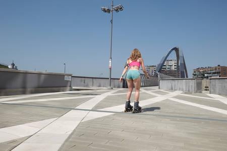 Skating woman on inline skate in urban environment