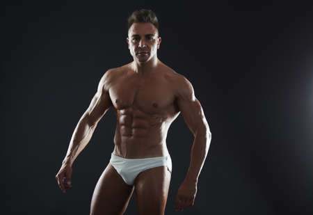 Handsome muscular fit young man on studio background