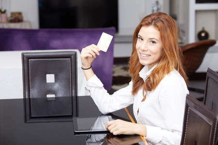 Pretty woman doing online shopping with laptop at home in the living room Stock Photo
