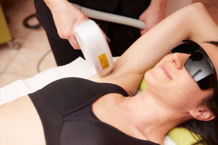Beautician Giving Laser Epilation Treatment To Young Woman's body At Beauty Clinic photo