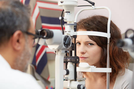 anesthetize: pretty young woman having her eyes examined by an eye doctor