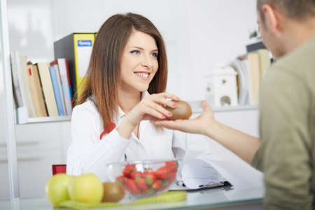 Smiling doctor nutritionist giving kiwi to male patient sitting at the desk with colorful fruits and vegetables Stock Photo